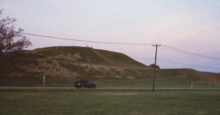 This photo does not do justice to the largest mound at Cahokia, though the car, telephone poles and human figure silhouettes give some sense of its size.