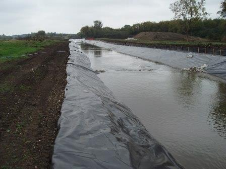 The temporary channel is lined with plastic to prevent erosion.
